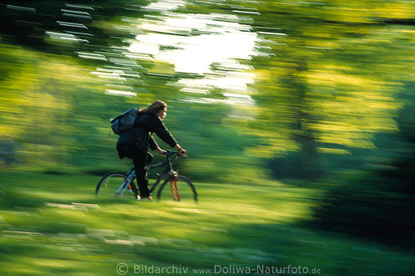 Cyclist speed-drive in blurred green-leaves bicycle-girl spring art-photo dynamic movement fuzziness picture
